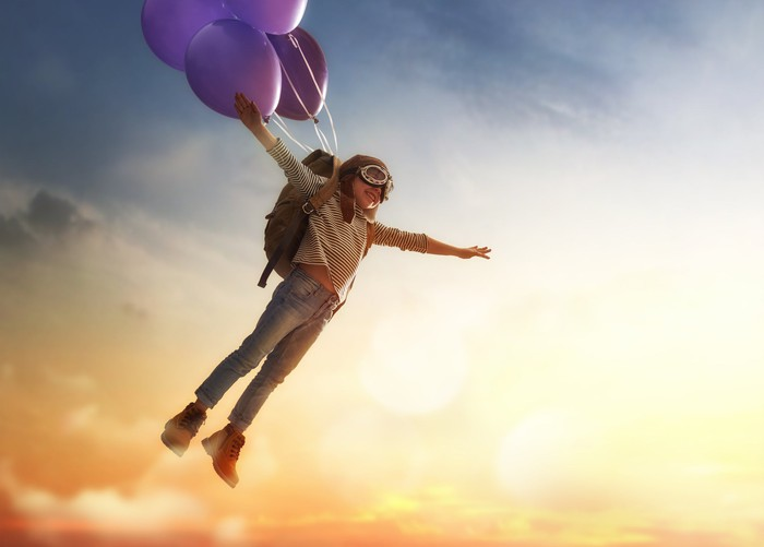With purple balloons attached to his backpack, a child, dressed as an aviator, flies through the air.