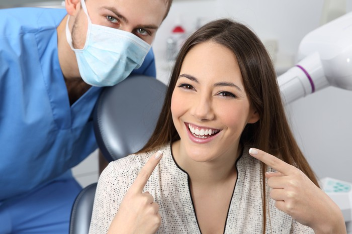 Dentist crouching down next to young female patient pointing to her smile with both index fingers.