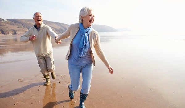 retired couple holding hands and running at the beach_GettyImages-510040759