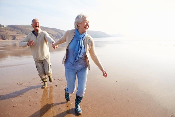 Senior couple holding hands on the beach.