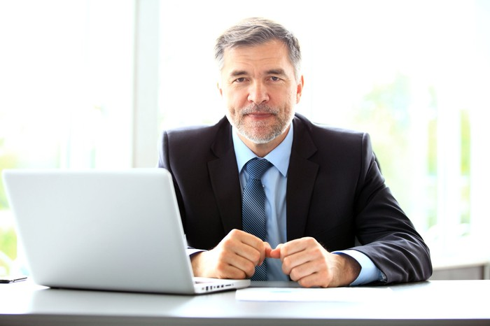 Older man in a suit with a laptop in front of him.