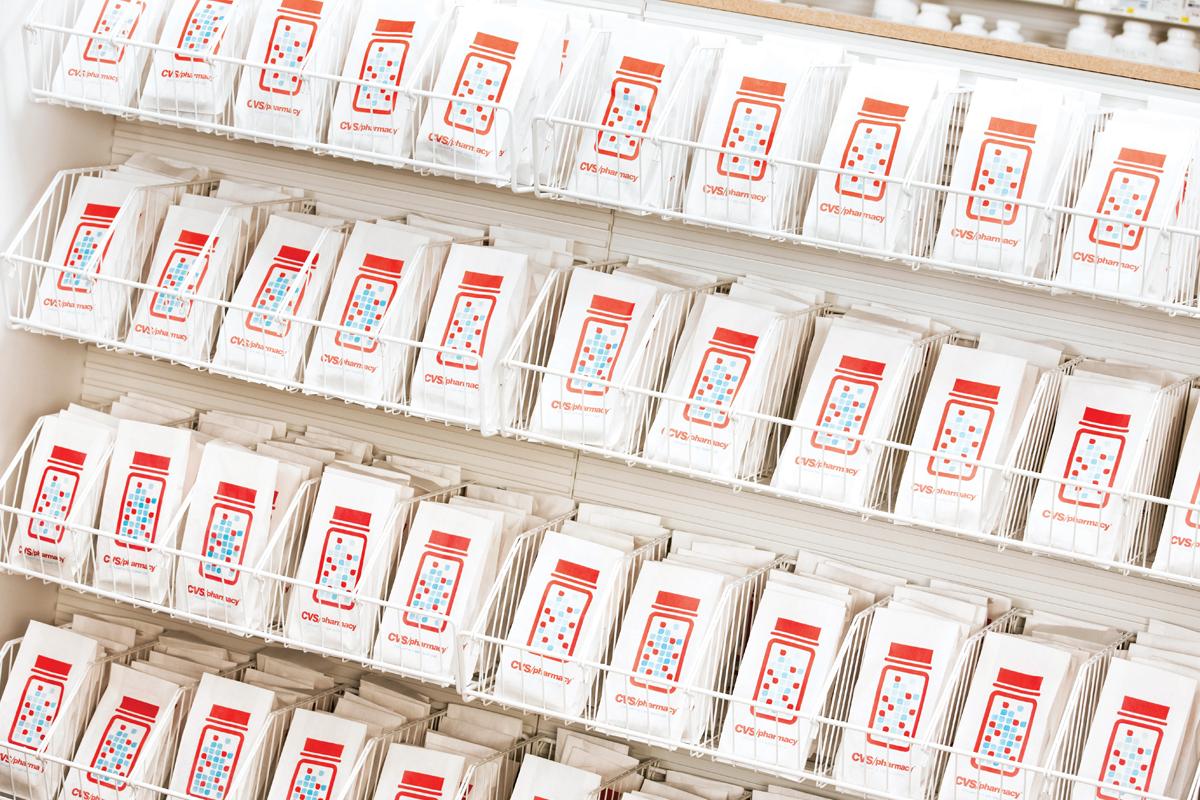 Row of prescription bags with the CVS pharmacy logo on them.