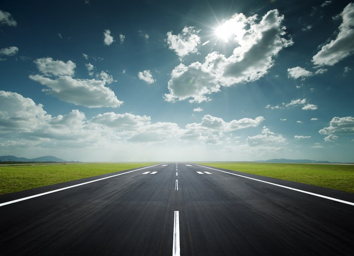 A sunny blue sky above a clear airport runway