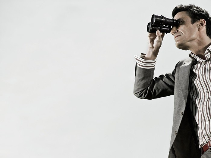 Man in a gray suit looking through binoculars.