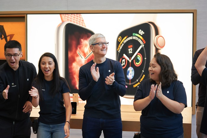 Tim Cook with two Apple employees to his right and one to his left.