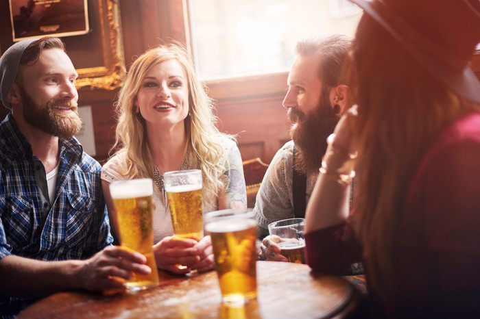 Two men and two women chatting over beers at a bar.