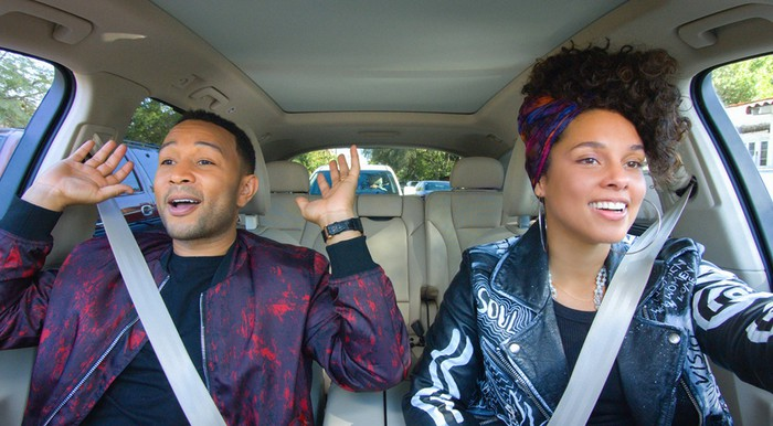 "A scene from an episode of ""Carpool Karaoke"" featuring John Legend and Alicia Keys singing in a car."