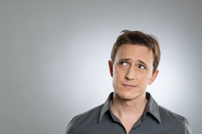 Man with confused expression against gray background.