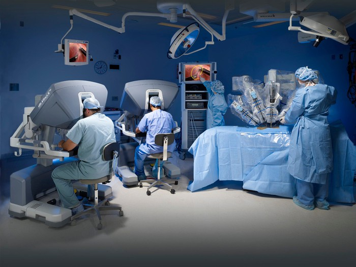 Two surgeons sitting at consoles in an operating room, conducting robotic surgery, with nurses in attendance