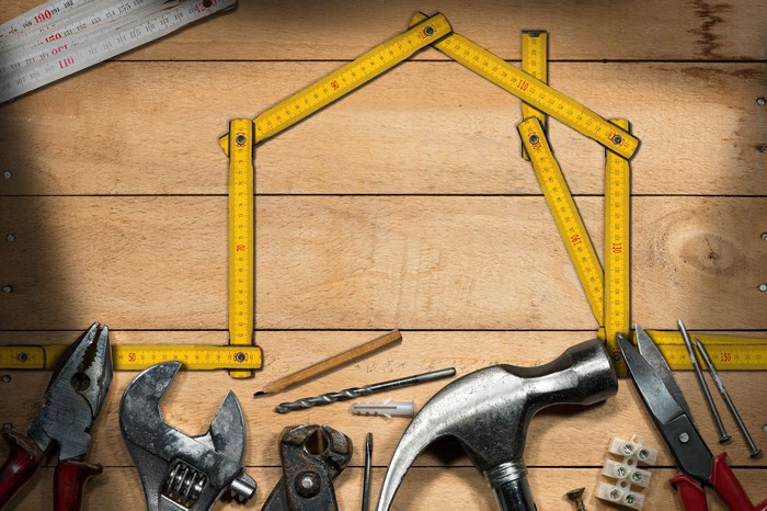 Home-improvement tools lined up under a yellow measuring tape shaped like the outline of a house.