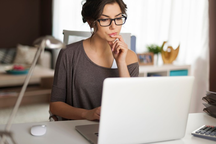 Woman at laptop deep in thought