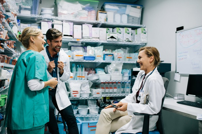 Three healthcare providers in a pharmacy.