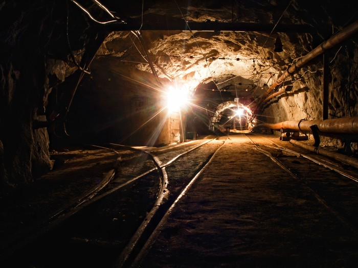 A mine tunnel with lights in the background