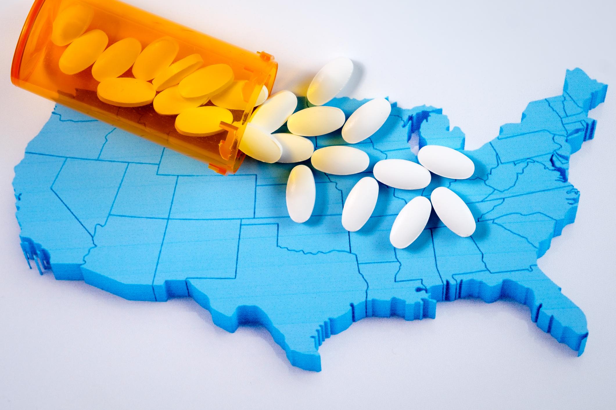 Translucent orange bottle spilling pills on top of a raised blue U.S. map