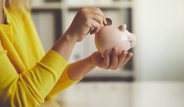 woman putting coin into piggy bank_GettyImages-884707970