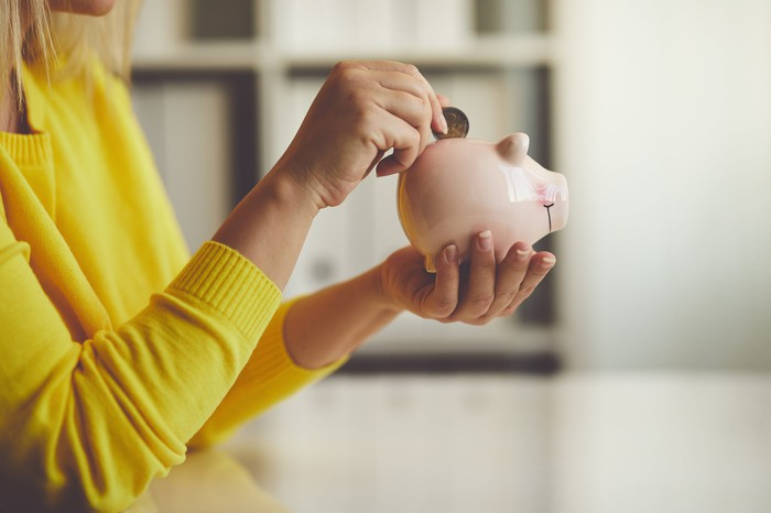 Woman putting a coin into a piggy bank.