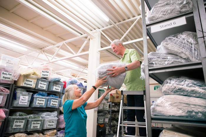 Senior man on a stepladder stocking warehouse shelves while woman assists.