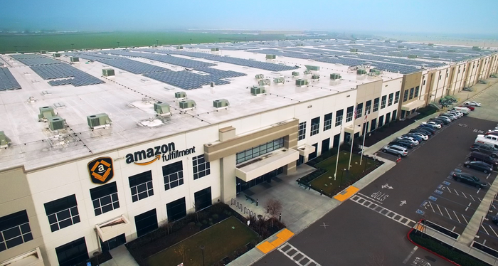A bird's eye view of an Amazon warehouse sporting solar panels on the roof.