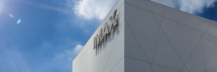 The top corner of a building with the IMAX logo against a bright blue sky with clouds.
