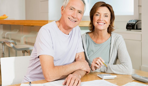 smiling senior couple with documents and calculator_GettyImages-517280133
