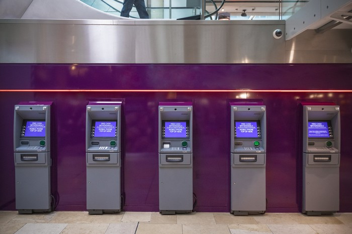 Bank of ATM machines in a conference center lobby.