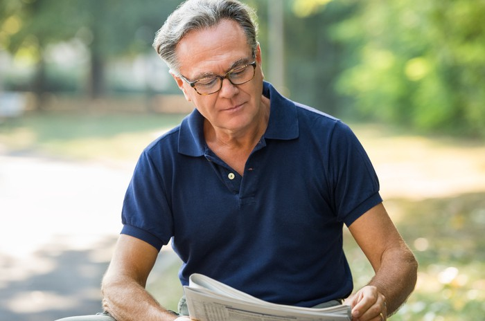 Older man reading a newspaper outdoors.