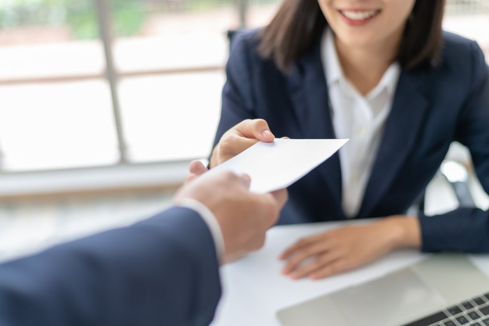 A person reaching out their hand to receive a check.