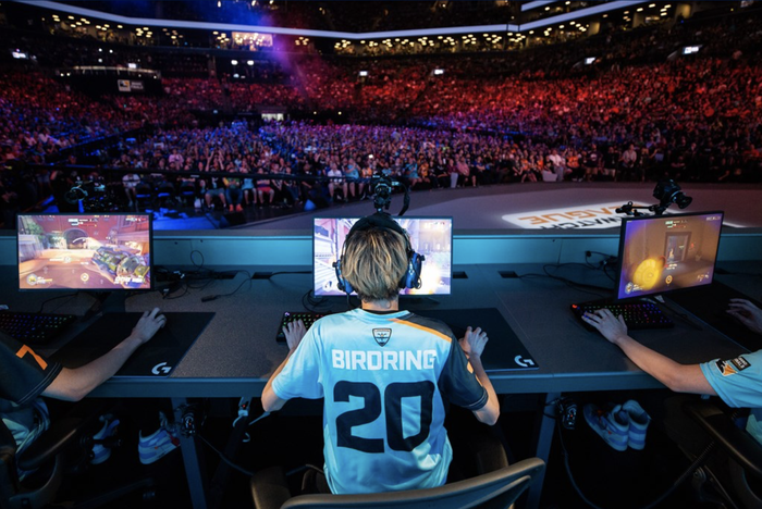 Professional esport player on a stage competing in front of a large audience in an arena.