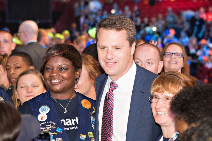 Walmart CEO Doug McMillon surrounded by employees.