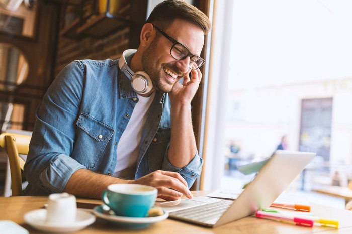 Smiling man sitting at laptop with headphones around his neck.