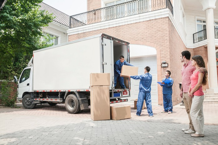 A man and a woman watches movers unpack a truck.