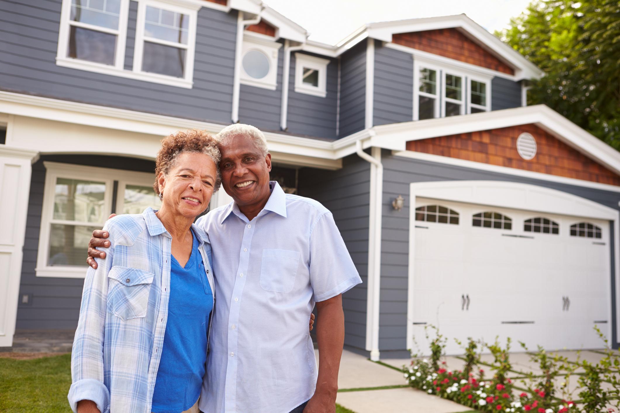 Senior couple standing outside a house.