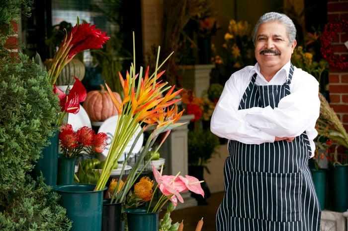 Smiling older man in apron outside a flower shop.
