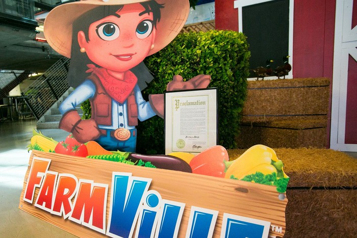 Cutout poster of FarmVille logo and character in front of a display set up in a mall.
