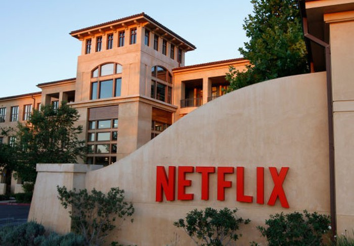 A photograph of the Netflix headquarters campus in Los Gatos, California, featuring a large Netflix logo on a wall in the foreground.