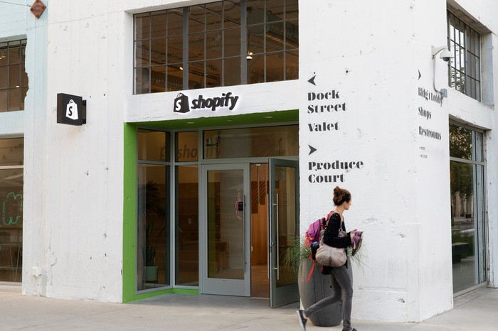 A young woman walks by the entrance of Shopify LA. The store is in a white concrete building and the company logo is above the door.