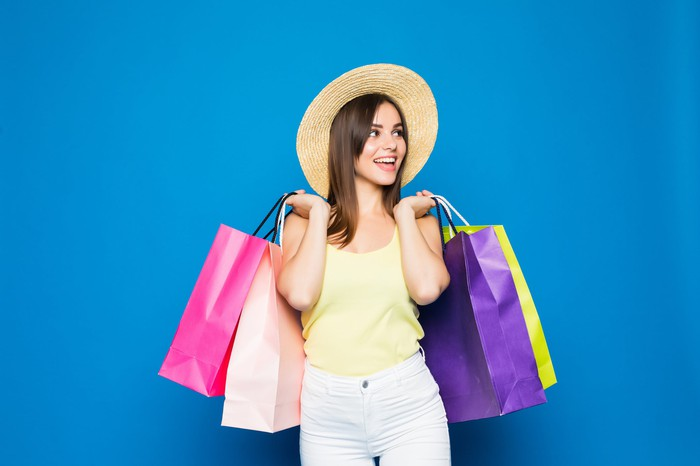 Woman carrying shopping bags against blue background.