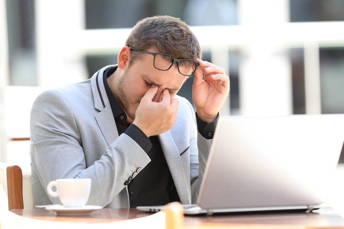A businessman, sitting at a bistro table with his laptop and some coffee, lifts his glasses to rub his eyes.