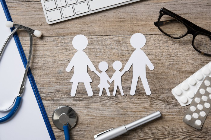 A paper cutout of a family on a desk next to a stethoscope, pills, a pair of glasses, a pen, and a keyboard.