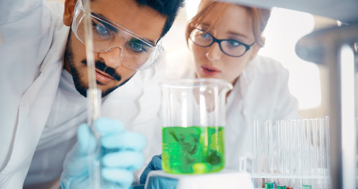 Two scientists in lab in front of a beaker containing green fluid.