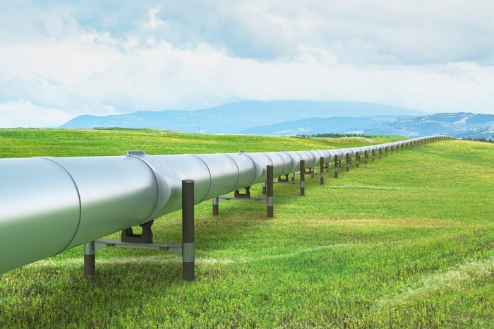 A pipeline on a green landscape heading toward the mountains.