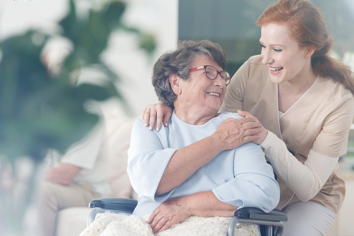 Older woman in wheelchair smiling and holding hands with younger woman in scrubs.