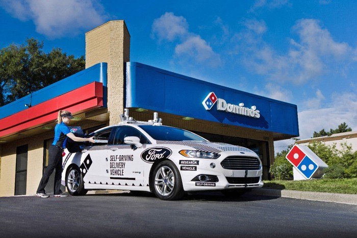 A white Ford Fusion with visible self-driving hardware is shown in front of a Domino's Pizza restaurant. A Domino's worker is loading a pizza into the vehicle.