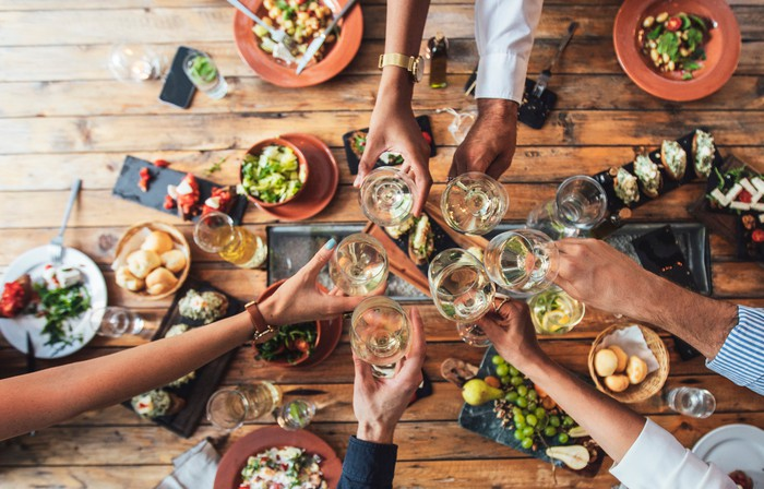 Image of people eating at table and toasting with wine.