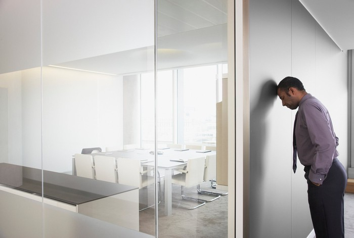 Man with head against wall in conference room.