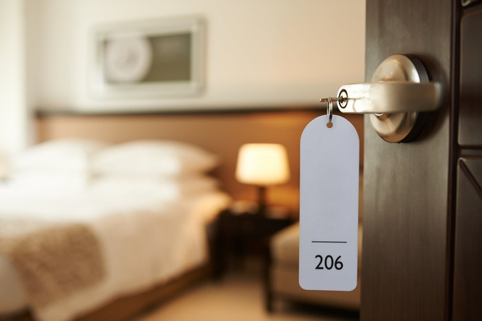 Key with attached room number keyfob inserted in lock on hotel room door.