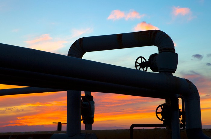 Sunset through the twists of a pipeline system