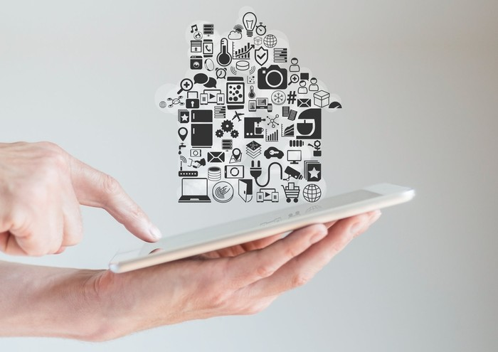 Person using a tablet with the outline of a house floating above it.
