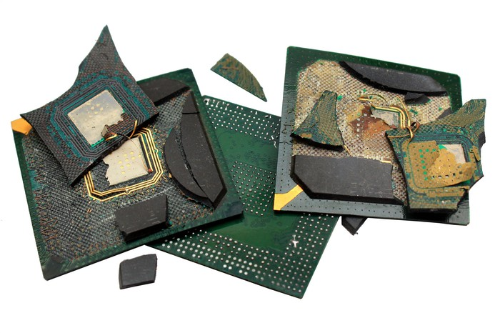Three PC processors, broken and charred, stacked in a loose pile.