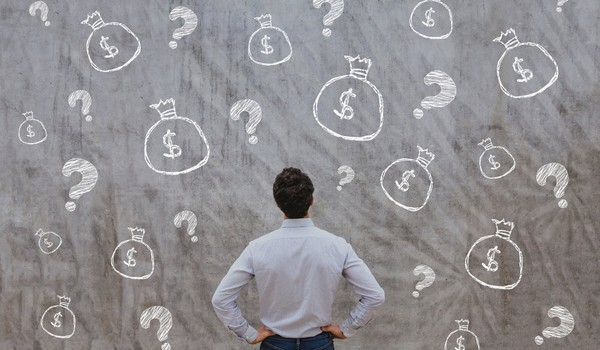man staring at wall covered by drawings of money bags and queston marks GettyImages-874031176